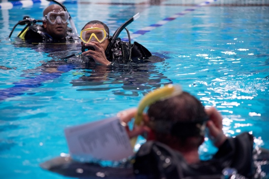 Scuba students Tionn Nelson, top left, and Aung Arkar await instructions from Scuba Diver trainer Frank Lewis (bottom) at the Columbia Swim Center. On Nov. 16, Columbia Scuba, Howard County's only scuba diving center, will host its final Scuba Splash Party of year, a chance for first-timers to get a taste of the activity. We take a look at how the water-based business grew up in a land-locked location and explore how it developed into a community of scuba divers.